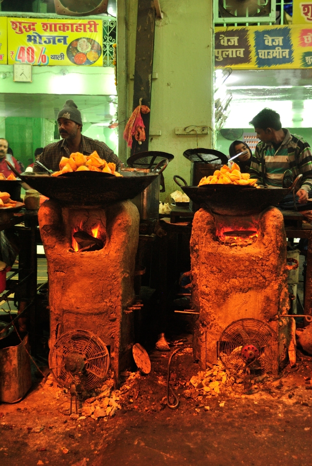 The cooks using huge ladles to get the piping hot samosas and kachoris from the wok and let the residual oil drip.