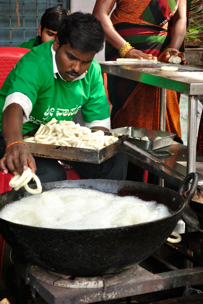 Kod Vadai being fried as the lady in the background rolls the dough and shapes it into circles.