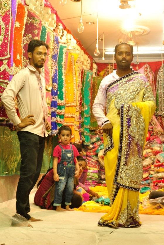 """Salesmen in Hyderabad don't have the least qualms in draping sarees and showing them off to customers. This young chap here beckoned me over to his shop and asked me to take a picture. """"Maidum"""", said his companion sitting off-camera, """"Don't take his face, you won't be able to see anything in print. Or just do some Photoshop on him, make him fairer."""" He grinned as I looked at him with bulging eyes, then at the saree-clad man. He just grinned too and posed some more for my camera."""